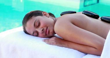 morena tranquila recebendo massagem com pedras quentes à beira da piscina video