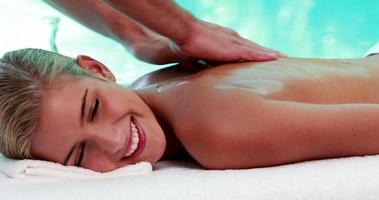 loira tranquila recebendo uma massagem à beira da piscina video