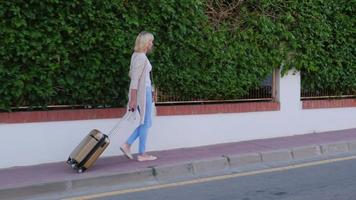 mulher com uma mala de viagem com rodas chega à porta do hotel. chegada ao hotel ou de férias video