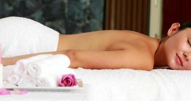 bella bruna sdraiato sul lettino da massaggio sorridendo alla telecamera