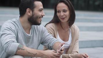 giovane uomo e donna sorridenti felici sono seduti sui gradini all'aperto e comunicano. video