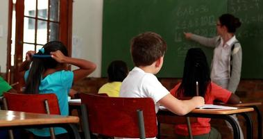 garotinho se virando para sorrir para a câmera durante a aula