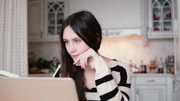 Porträt einer schönen jungen brünetten Frau verwendet Laptop in einem hellen Essen