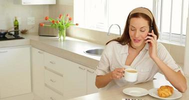 hübsche Frau, die beim Frühstück telefoniert
