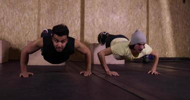 Deux homme dans le sport de gym exerçant les jeunes gars faisant la formation de gym push ups presse, sportif travaillant