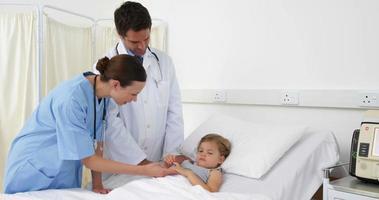 niña enferma acostada en la cama hablando con la enfermera y el médico