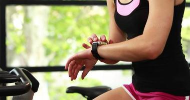 mulher em forma usando bicicleta ergométrica e relógio inteligente