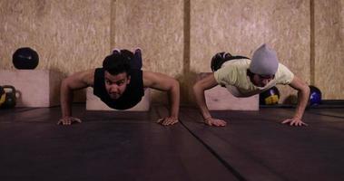 due uomini nello sport della palestra che esercitano giovani ragazzi facendo press push up palestra formazione, sportivo lavorando
