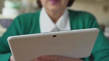 Close up of a white tablet PC in a aged woman hands - Front view