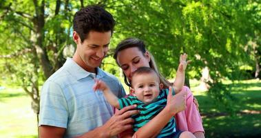 Young couple holding baby son smiling at camera in park