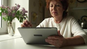 Femme âgée à l'aide d'une tablette numérique à la maison