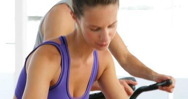 coppia in forma che esercitano sulle bici in studio fitness