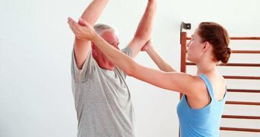uomo più anziano di sollevamento pesi a mano con l'aiuto del fisioterapista