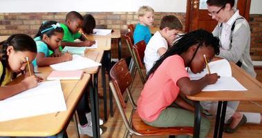 élèves travaillant dur pendant la classe avec enseignant souriant à la caméra