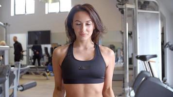 Mujer haciendo flexiones de bíceps con pesas en un gimnasio, vista frontal, filmada en r3d