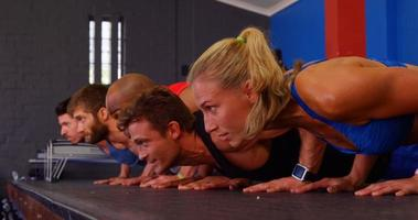 grupo de pessoas fazendo exercícios de flexão video