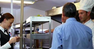 datore di lavoro che guarda chef che prendono ordini