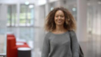 Smiling female university student walking into focus indoors