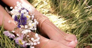 Girl's feet in green grass with flowers and foot jewellery video