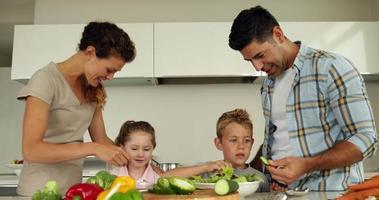 parents préparant une salade avec leurs enfants video