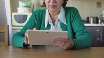 donna matura utilizza un tablet pc bianco a casa - vista frontale