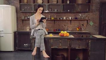 Female with modern device spends morning in flat video