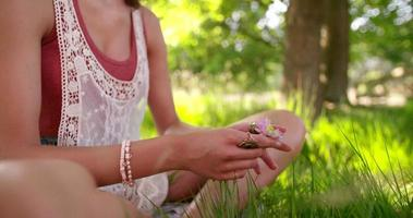 Girl holding a flower while sitting in a summer park video