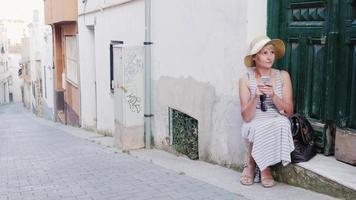 turista de mulher usa smartphone. ele está sentado na soleira de uma velha casa na cidade turística. conceito - problemas viajantes