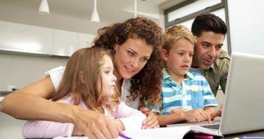 süße Kinder, die mit Eltern am Tisch zeichnen und Laptop verwenden