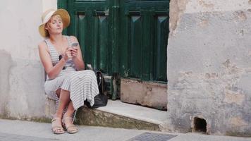 vrouwelijke toerist zittend op een parade van de oude huisdeur. met behulp van mobiele telefoon