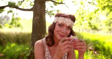 Smiling hippie girl in a park holding wild flower video