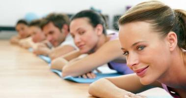 lezione di fitness sdraiato su stuoie sorridendo alla telecamera