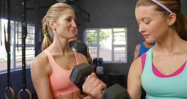 Fitness trainer assisting woman with dumbbell video