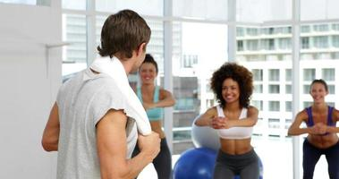 Fitnessklasse hockt auf Bosu Bällen video