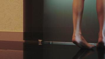 Fille aux jambes nues à pied de la salle de bain porte ouverte et asseoir sur une baignoire blanche