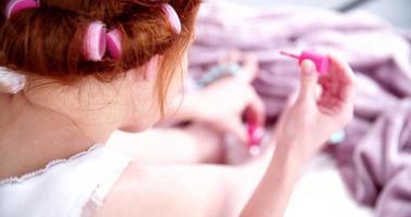 chica con rulos en el pelo pintándose las uñas de los pies video