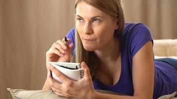 bela jovem atraente em uma camiseta violeta, escrevendo em um caderno. fazendo uma lista, pensando e sorrindo video