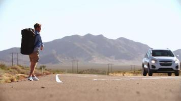 due uomini in vacanza in autostop lungo la strada girato su r3d