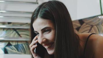 portrait de jeune fille brune parlant au téléphone dans la salle de bain. maquillage