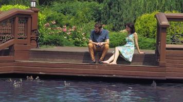 Paar sitzen auf einer Holzbrücke und schauen auf den See, wo Enten schwimmen