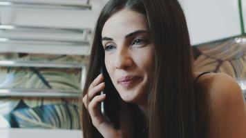 Porträt des attraktiven Mädchens der Brünette, das am Telefon im Badezimmer spricht. bilden