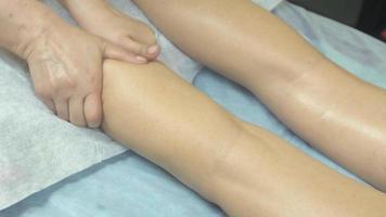 massagista faz massagem relaxante da perna direita, tornozelo para mulher no salão. acariciando video