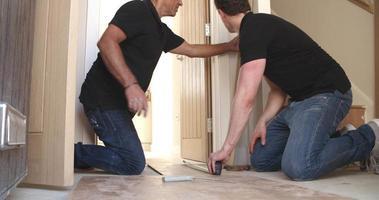 Dos hombres colocando pisos de paneles de madera laminada en una casa video