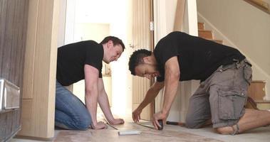 due uomini che posano pavimenti in pannelli di legno laminato in una casa