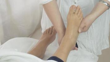 la massaggiatrice fa il massaggio del piede destro alla donna nel salone. cura della pelle. terapia