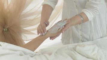 Kosmetikerin legte Tonmaske auf Hand erwachsene Frau, bedeckt es mit Fäustling im Salon