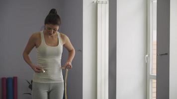Frau misst die Taille im Fitnessstudio