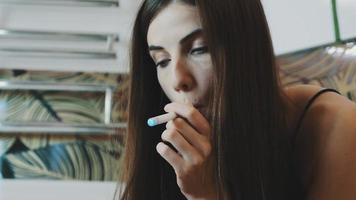 Porträt des jungen Mädchens sitzen im Badezimmer mit Telefon und rauchen elektronische Zigarette