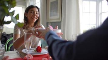El hombre le da a la mujer un regalo en la comida romántica del día de San Valentín video