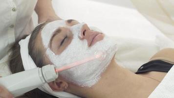Cerrar cara de niña darsonvalization con máscara en el salón. procedimiento cosmético